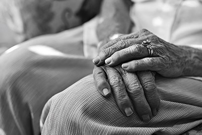 A picture of two elderly hands, one crossed over the other on the person's lap.